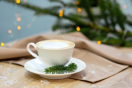 Delicious cappucino coffee cup . fireflies and spruce branches