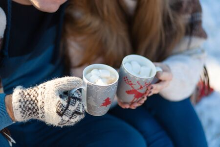 Young couple in love drink a hot drink with marshmallows, sitting in the winter in the forest, tucked in warm, comfortable rugs and enjoy nature.
