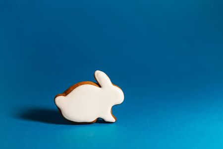 gingerbread cookie of white rabbit on blue background. Traditional Christmas food. Christmas and New Year holiday concept. Copyspace.