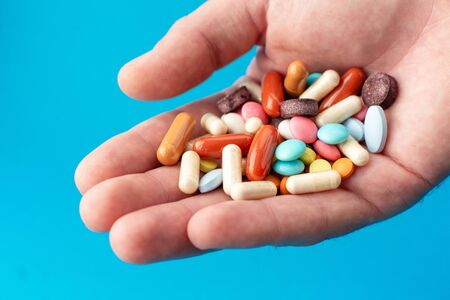 A handful of colored pills on the palm. Medical concept. Shopping at the pharmacy