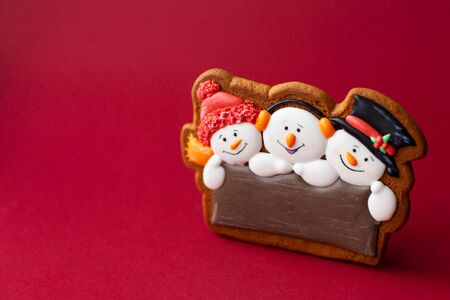 gingerbread cookie of cute snowman on red background. Traditional Christmas food. Christmas and New Year holiday concept