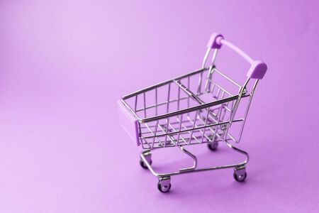 empty metal shopping trolley on purple background. Discount and shopping concept. Reklamní fotografie
