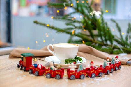 Delicious fresh festive morning cappuccino coffee in a ceramic white cup on the wooden table with decorative christmas train, red ornamentals, fireflies and spruce branches. Reklamní fotografie