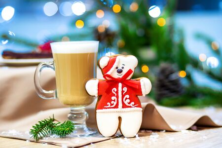 Delicious cappucino glass cup with christmas teddy bear gingerbread cookie. fireflies and spruce branches background