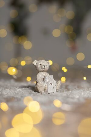 Decorative figurines of a Christmas theme. Statuette of a teddy bear with a scarf, sit next to the box with a Christmas present. Christmas tree decoration. Festive decor, warm bokeh lights