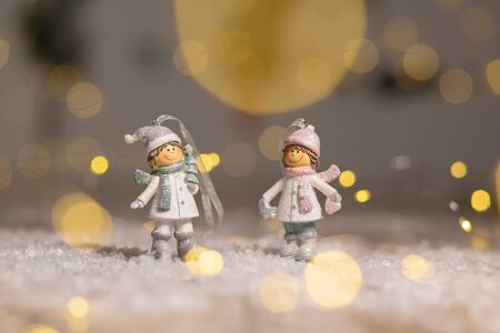 Decorative Christmas-themed figurines. Statuette boy and girl in knitted hats and scarves. Christmas tree decoration. Festive decor, warm bokeh lights Reklamní fotografie