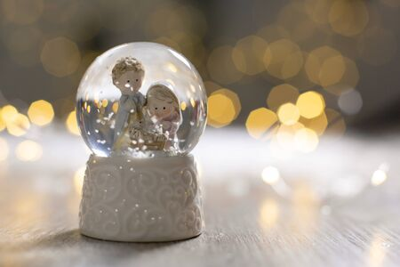 Decorative Christmas-themed figurines. A glass ball with snowflakes in which two men are looking at the cradle, a symbol of the Nativity of Christ. Christmas tree decoration. Festive decor, warm bokeh lights Reklamní fotografie