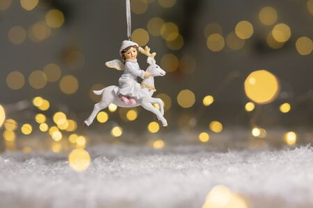 Decorative figurines of a Christmas theme. Figurine of an angel rides on a white deer. Christmas tree decoration. Festive decor, warm bokeh lights