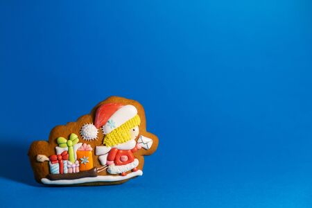 gingerbread cookie of little cute Santa postman on blue background. Traditional Christmas food. Christmas and New Year holiday concept. Copyspace. Stock Photo
