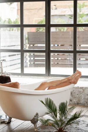 A gorgeous woman is enjoying herself in a white bathtub, in a bright room with a large window Stock Photo