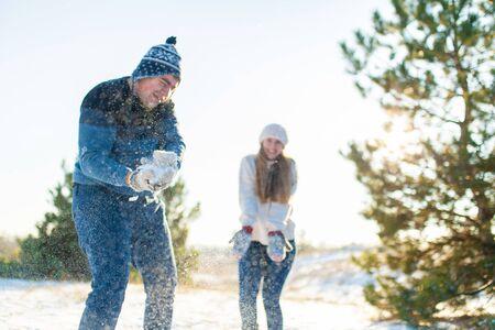 Un couple d'amoureux joue aux boules de neige en hiver dans la forêt. Jetez-vous de la neige. Riez et passez un bon moment.