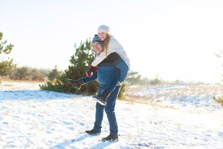 Loving couple play in the winter in the forest. Girl rides a guy in the background of the Christmas tree. Laugh and have a good time.