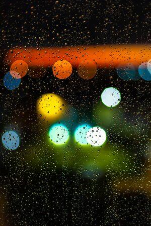 Water drop at windows and bokeh of city in sunset. Banco de Imagens