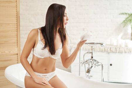 Sexy girl in lingerie whip soap foam in the bath and blows it off her hands Stock Photo