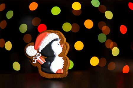 gingerbread cookie of little penguin with gift over defocused colored lights of garland. Traditional Christmas food. Christmas and New Year holiday concept