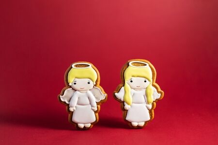 gingerbread cookie of little cute angels on red background. Traditional Christmas food. Christmas and New Year holiday concept