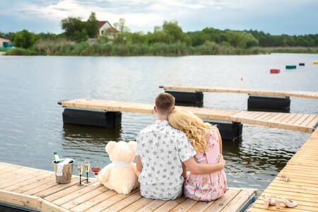 Romantic date surprise. A young guy and a girl on a wooden pier. Hug and kiss while sitting on the pier. Romantic love story.