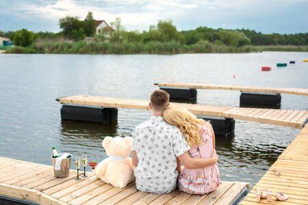 Romantyczna niespodzianka na randkę. Młody chłopak i dziewczyna na drewnianym molo. Przytul i pocałuj siedząc na molo. Romantyczna historia miłosna.