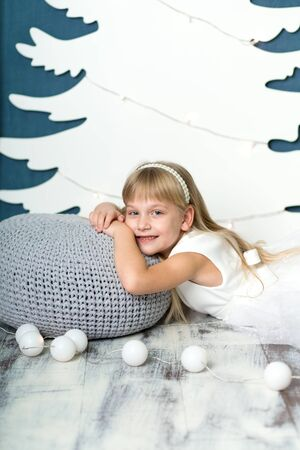 A little girl lies smiling on a pillow covered with a gray knitted blanket, against the background of an artificial white Christmas tree decor from cardboard, and next to it lies a garland