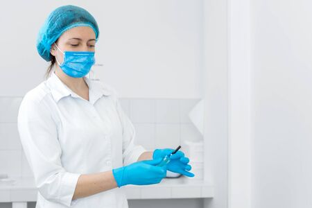 gloved nurse removes sterile needle from packaging.