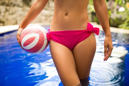 Slender girl model in a sexy pink swimsuit plays ball in a tropical pool in the jungle Imagens