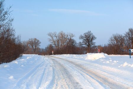 Winter poorly cleared road. Road in the countryside strewn with snow. Winter landscape with snowdrifts.