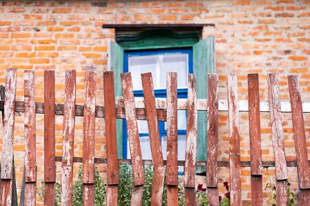 Shabby fence from the boards against the background of an old house. Typical village architecture.