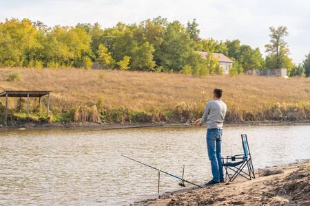Man relaxing and fishing by lakeside.