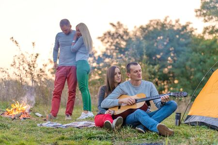 Group of happy friends with guitar, having fun outdoor, near bonfire and tourist tent. Camping fun happy family.