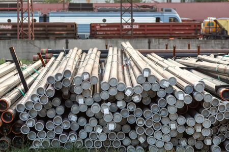 Metal rolling. Pipes folded in a railway warehouse are being prepared for shipment. The concept of metalworking and heavy industry.