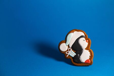 gingerbread cookie of cute penguin with gift on blue background. Traditional Christmas food. Christmas and New Year holiday concept