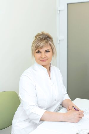 Portrait of a blonde doctor woman in a white coat sitting at a table in a medical office.