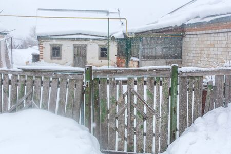 Winter in the village. Old dilapidated rickety fence of wooden boards. A lot of snow around. Stock Photo