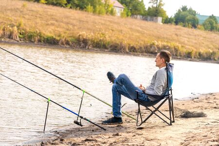 a Man relaxing and fishing by lakeside.