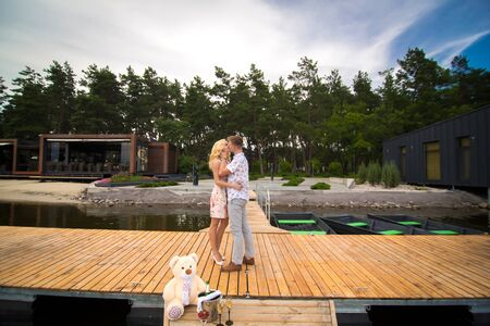 Loving young couple kisses on a wooden pier. Lovestory on the pier.