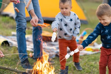 travel, tourism, hike, picnic and people concept - group of happy friends with kids frying sausages on campfire