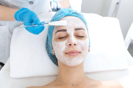 Estetista medico professionista donna applica una maschera sul viso di un paziente per la cura della pelle. Procedure cosmetiche per il ringiovanimento e la nutrizione della pelle.