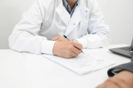 El doctor toma notas en el historial médico de un paciente. Foto de archivo