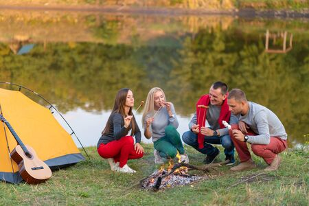 travel, tourism, hike, picnic and people concept - group of happy friends frying sausages on campfire near lake Banque d'images