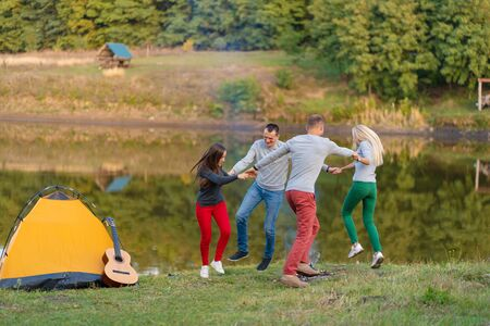 Group of happy friends with guitar, having fun outdoor, dancing and jumping near the lake in the park background the Beautiful sky. Camping fun.