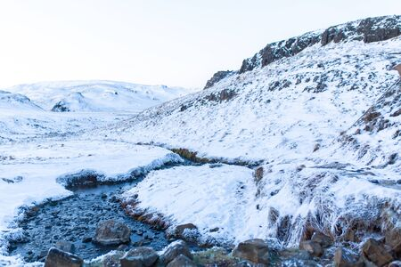 Incredible winter landscape of Iceland. In winter, a source of hot water flows in the mountains.