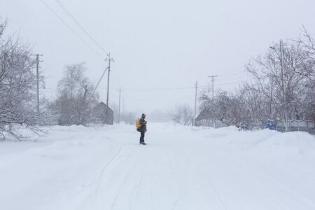 A rustic man is walking down the street in winter with a yellow backpack. Snow blizzard. Reklamní fotografie