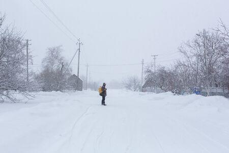 Un uomo rustico cammina per strada in inverno con uno zaino giallo. Bufera di neve. Archivio Fotografico