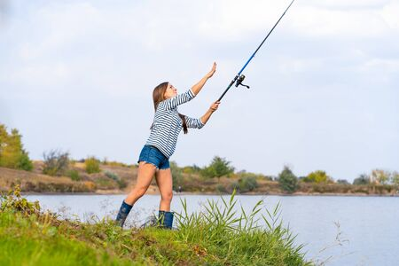 Beautiful young girl fishes on the lake