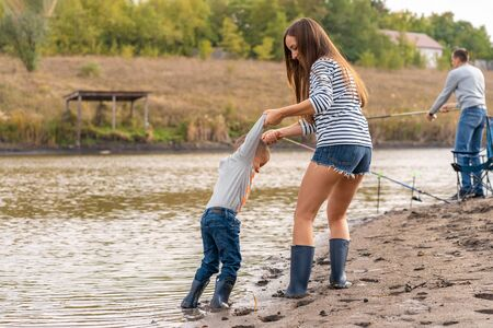 Mom with a small son walks along the sandy shore of the lake in rubber boots. Hanging out with children in nature, away from the city.