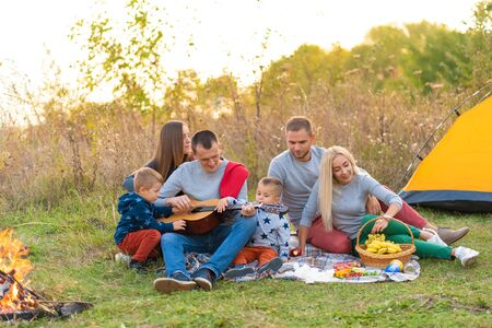 travel, tourism, hike, picnic and people concept - group of happy friends with tent and drinks playing guitar at camping. Stock Photo
