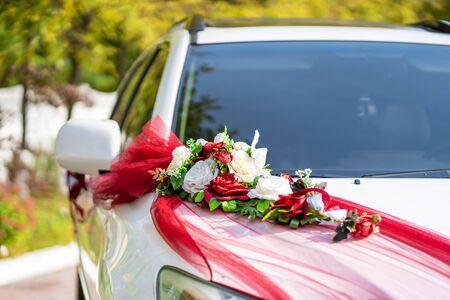 White wedding car decorated with fresh flowers. Wedding decorations