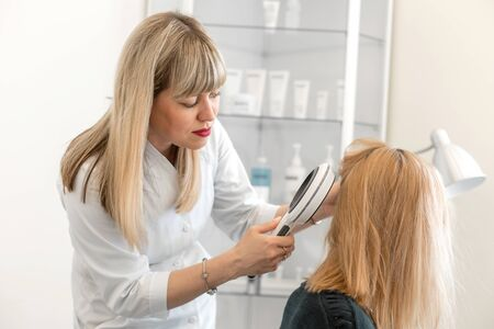 A trichologist examines the condition of the hair on the patient head with a dermatoscope. In a bright cosmetology room.