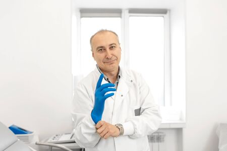 Portrait of a urologist doctor putting on medical gloves before examining a patient. Stock Photo
