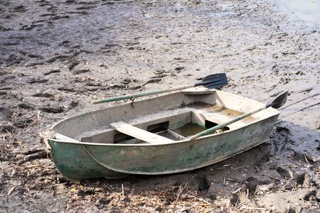 A metal boat with oars on the river bank. Fishing season. Stockfoto